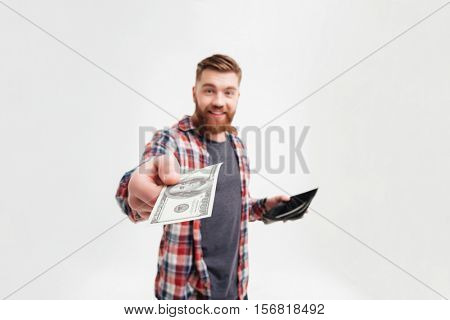 Cheerful smiling bearded man in plaid shirt giving money from his wallet, focus on money