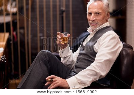 Satisfied with bargain. Handsome well-dressed old man sitting on leather armchair with cognac glass and cigar.