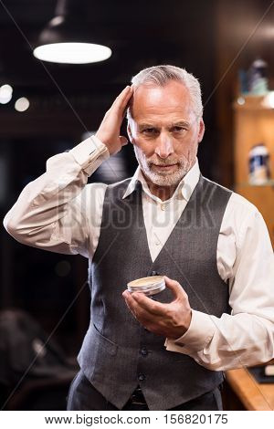 Smooth and perfect. Elegant handsome senior man bearded man styling hair with gel while standing in front of mirror.