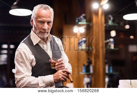 High status. Portrait of elegant handsome senior bearded man standing with whiskey glass and cigar at barbershop.