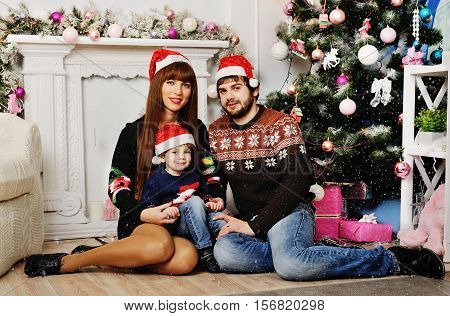 mother, father and little boy with red Christmas hat on fonee rozhdestenskoy tree