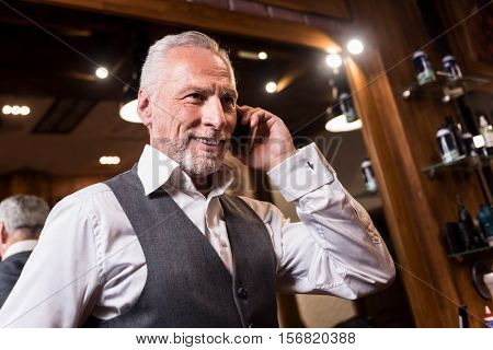 Discussing important bargain. Low angle of nice smiling senior businessman standing and talking on mobile phone.