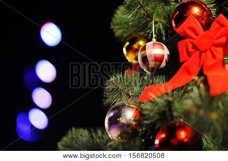 Christmas background with Christmas tree, Christmas ornaments and a big red bow