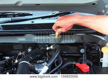 Man checking oil in his car using dipstick