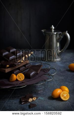 various sorts of dark chocolate bars, kumquats and a small silver coffee jug on a table against a dark background