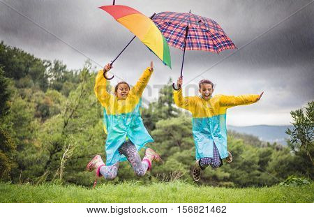 Children with colorful rainbow umbrellaraincoats and waterproof boots jump in the rain