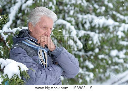 Portrait of thoughtful senior man in a snow-covered winter park
