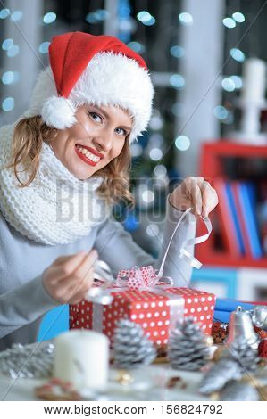 Happy young beautiful woman in santa hat unwrapping her Christmas present