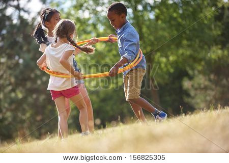 Kids happily playing with hula hoop in summer