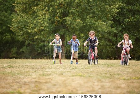 Children at the park racing with their bikes and scooter
