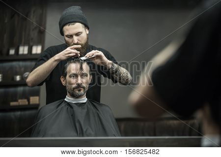 Careful barber with a big beard and a tattoo is combing the hair of the bearded man in the black hair cutting cape in the barbershop. He also fixes client's strands with the hairgrips. Horizontal.