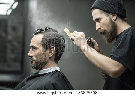 Stylish barber with a big beard splashes from the spray bottle at the hair comb next to his client's head in the barbershop. He wears a black T-shirt with a black cap. Customer wears a black cape.