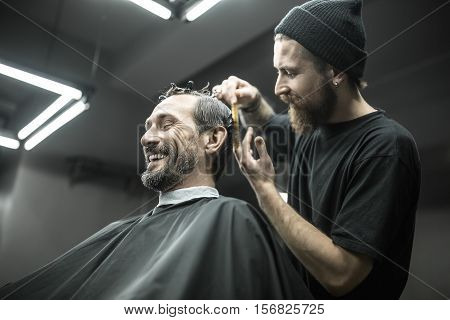 Laughing bearded man with closed eyes in the black cutting hair cape in the barbershop. He has hairgrips on his head. Pleased barber in a black T-shirt and a cap is doing the haircut. Horizontal.