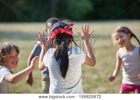 Happy kids playing blind man's buff at a birthday party