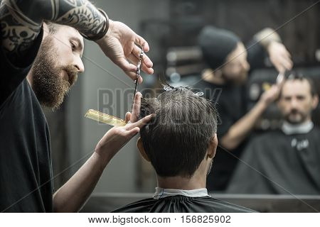 Unmatched barber with a big beard is cutting the hair ends of his client in the black cutting hair cape in the barbershop. Customer has hairgrips on the head. The both blurry reflected in the mirror.