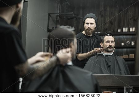 Man and a barber reflected in a mirror in the barbershop. Hairdresser wears a black T-shirt with a cap and has a hair comb. Client wears a black cutting hair cape and has hairgrips on his head.