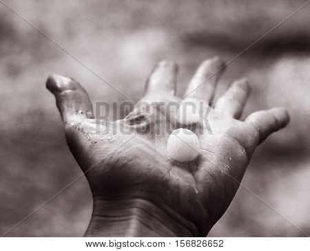 hail lay on the human palm black and white phto