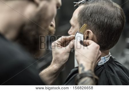 Unapproachable barber with a beard and a tattoo is cutting the hair of his client in the barbershop. He is using a cutting comb and a hair clipper. Customer has hairgrips on the head. Closeup.
