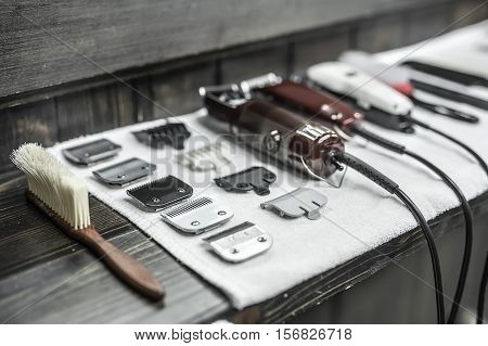 Closeup photo on the wide aperture of the hairdresser accessories: a wooden hairbrush, clipper blades, hair clippers and hair combs. They lies on the white towel and the dark wooden rack. Horizontal.