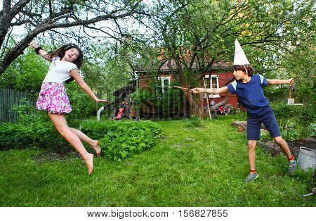 siblings boy and girl play harry potter game with magic stick