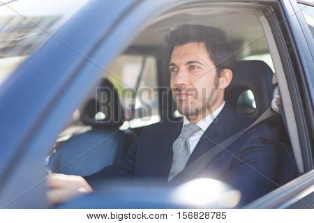 Portrait of an handsome businessman driving his car