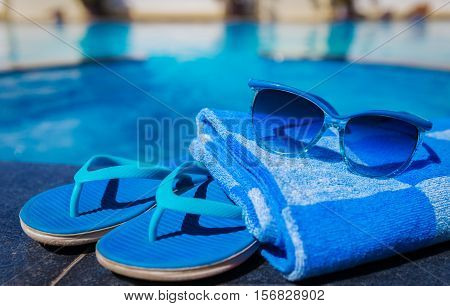 Blue slippers, sunglasses and towel on border of a swimming pool - holiday tropical concept