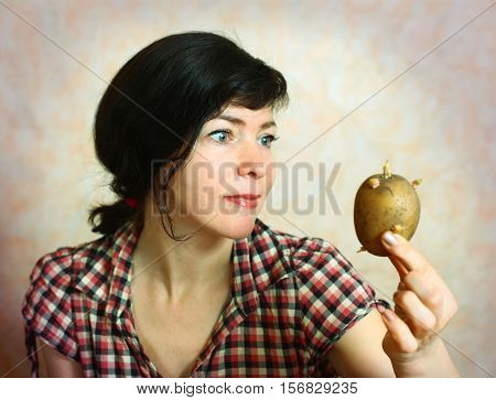 pretty houswife with sprouted potato close up
