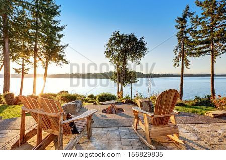 Back Yard Of Waterfront House With Adirondack Chairs And Fire Pit