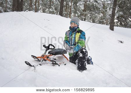 In winter the snow-covered forest boy rode from the mountain and fell with the sledge
