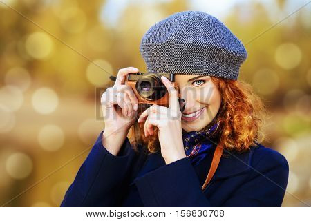 Autumn style. Beautiful smiling woman with bright foxy hair wearing beret and black coat photographs. Beauty, fashion.