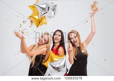 Three cheerful joyful young women with star shaped balloons and confetti having party together over white background