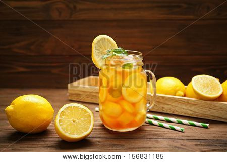 Glass jar of iced tea with lemon slices and mint on wooden table