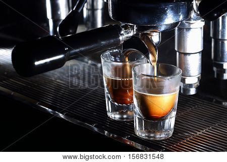 Professional Espresso Machine Brewing A Coffee. Coffee Pouring Into Shot Glasses