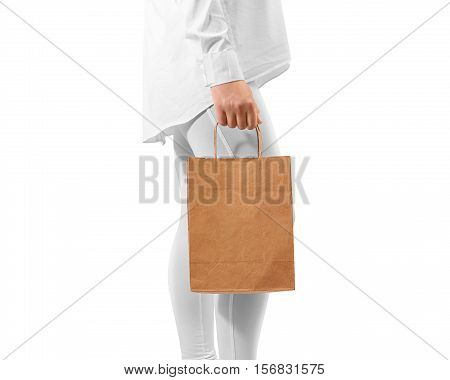 Blank brown craft paper bag design mockup holding hand, clipping path. Woman hold kraft textured bundle mock up. Clear gift bagful branding template. Shopping carry package person arm. Handmade sac