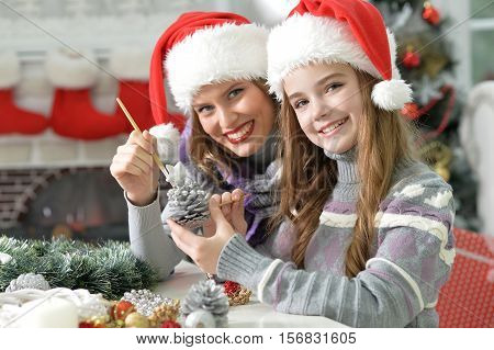 Portrait of happy young mother and her daughter in Santa hats  coloring pine cone for decorating