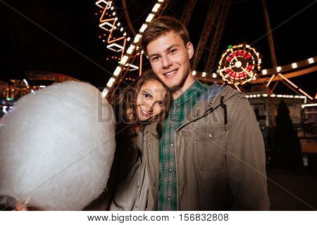 Beautiful young couple with cotton candy standing and hugging in amusement park