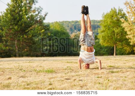 Activ senior man making a headstand in summer in the park
