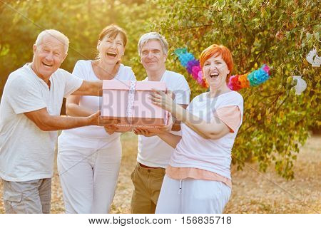 Seniors laughing and smiling with a birthday present at a party