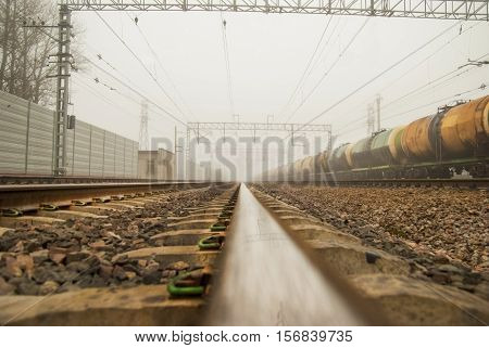 Railway to infinity. Railcars in cloudy day in the fog