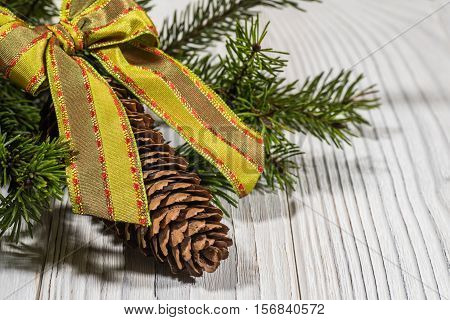 Christmas background: spruce twigs and cones on white board. Selective focus.