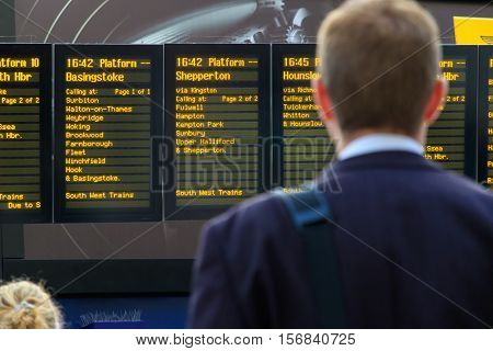 London UK - October 18 2016 - Commuter checking timetables at a train station