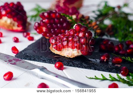 Half pomegranate and pomegranate seeds and a branch of spruce on white wooden background.