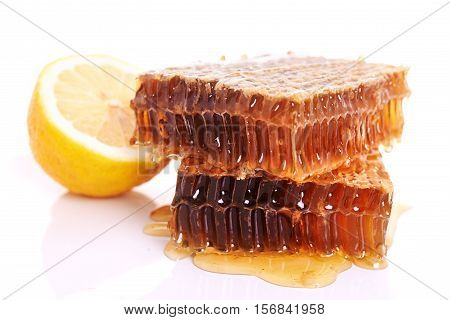 yellow honeycomb with fresh honey over white backgrounnd