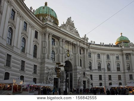 VIENNA, AUSTRIA - DECEMBER 31 2015: Main entrance of Hofburg Palace from Michaelerplatz with people and Christmas markets around