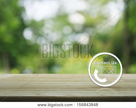 Telephone and mail icon button on wooden table over blur green tree background Contact us concept