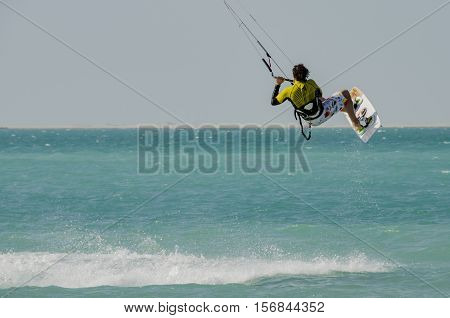 Kite surfer catching air over turquoise blue sea
