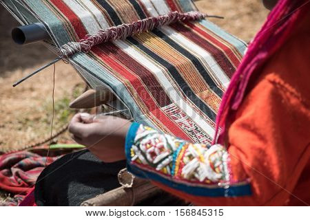 Peruvian lady weaving alpaca wool in traditional method