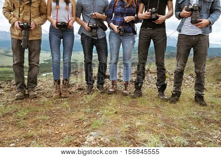Group of travel photographers stands on line with cameras in hands. Team and teamwork concept