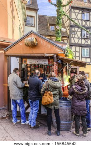 ColmarFrance-December 62013: People gathered near a stall for drinking mulled wine in a Christmas Maket in Colmar Alsace on December 62013.
