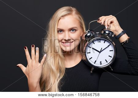 Hand counting - number five. Smiling woman holding big alarm clock showing five fingers, portrait over grey background